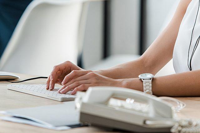 Bild Frau an Tastatur mit Telefon